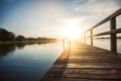 Saulės spinduliai atsispindi nuo vandens